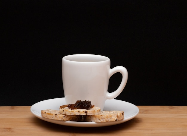 Filiżanka kawy obok ryżowych wegańskich ciasteczek z galaretką na wierzchu pod drewnianym stołem
