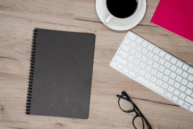 Filiżanka kawy, okulary, czarny notatnik i klawiatura