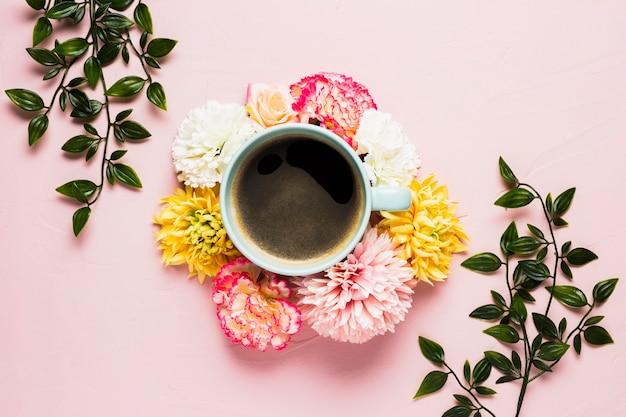Filiżanka kawy otoczona kwiatami