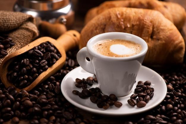 Filiżanka kawy otoczona ziarnami kawy z bliska