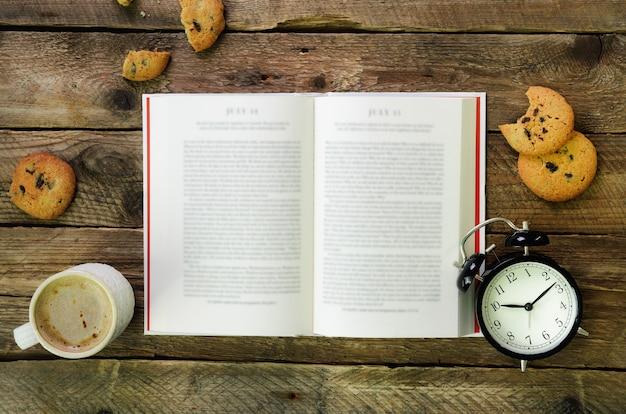 Filiżanka kawy, otwarta książka, budzik, ciastko na drewnianym rustykalnym roczniku.