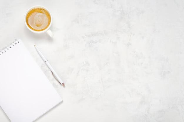 Filiżanka kawy, otwarty notatnik i długopis na jasnym tle betonu. widok z góry miejsca pracy. skopiuj miejsce