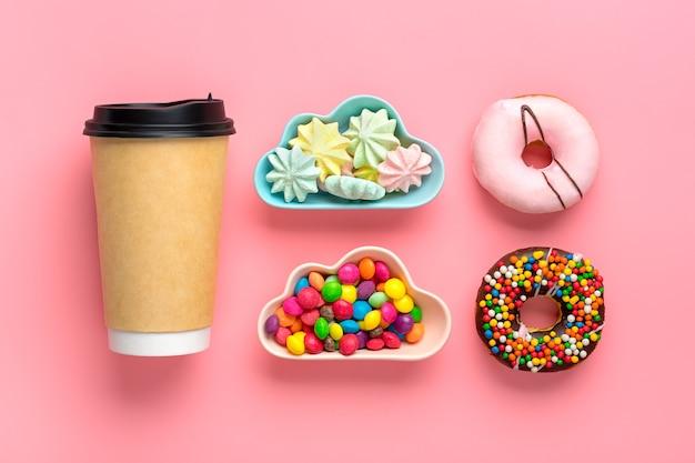 Filiżanka kawy, pączki i bezy w misce na białym tle