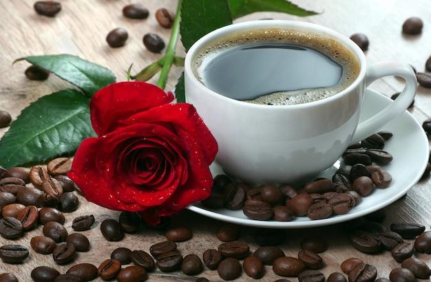 Filiżanka kawy, palone ziarna kawy i czerwona róża na drewnianym stole. romantyczna kawa.