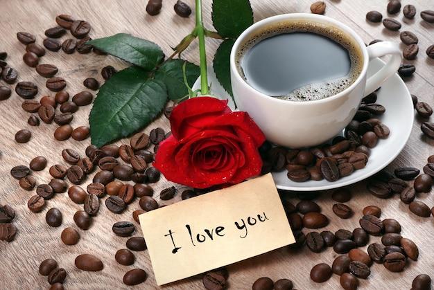 Filiżanka kawy, palone ziarna kawy i czerwona róża na drewnianym stole