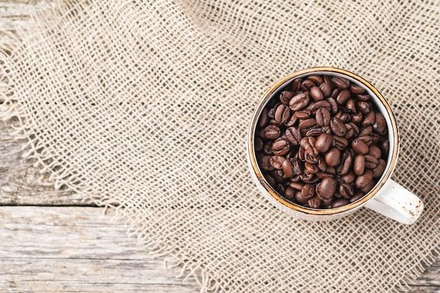 Filiżanka kawy pełna ziaren kawy z miejsca na kopię. widok z góry.