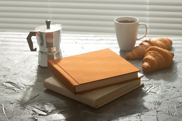 Filiżanka kawy po turecku i rogaliki z dwiema książkami na stole