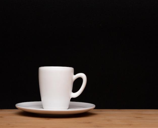 Filiżanka kawy pod drewnianym stołem