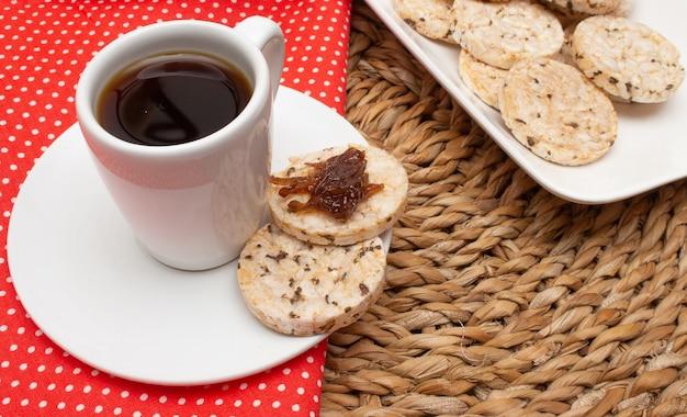 Filiżanka kawy pod słomianym stołem otoczona miską pełną ciasteczek ryżowych i dzbankiem do kawy