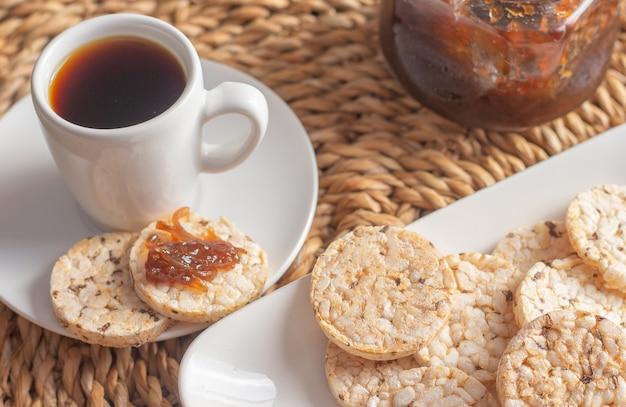 Filiżanka kawy pod słomianym stołem otoczona miską pełną ciasteczek ryżowych i dzbankiem z galaretką
