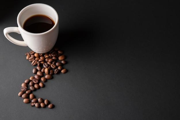 Filiżanka kawy pod wysokim kątem z palonymi ziarnami
