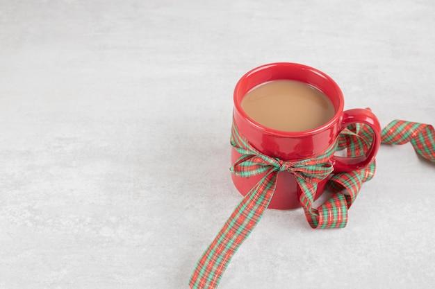 Filiżanka kawy przewiązana wstążką na białej powierzchni