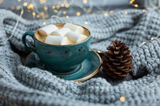 Filiżanka kawy, ptasie mleczko, ciepły sweter z dzianiny. ciepłe światła bokeh