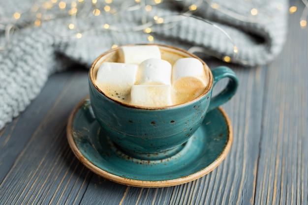 Filiżanka kawy, ptasie mleczko, ciepły sweter z dzianiny na drewnie