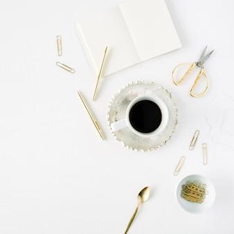 Filiżanka kawy, pusty pamiętnik i złote akcesoria: łyżeczka do herbaty, długopis, klipsy i nożyczki na białym tle