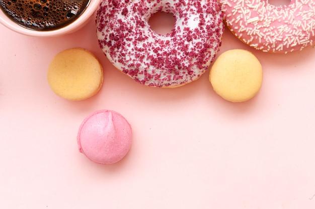 Filiżanka kawy, pyszne różowe pączki z posypką i kolorowe jasne macarons