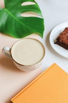 Filiżanka kawy raf z książką, monstera i brownie