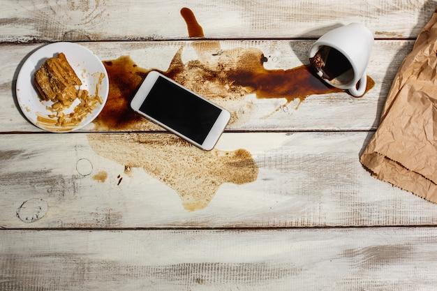 Filiżanka kawy rozlana na drewnianym stole