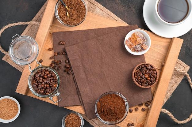 Filiżanka kawy, różne rodzaje kawy i cukier w filiżankach na brązowej ścianie. widok z góry z miejsca na kopię.