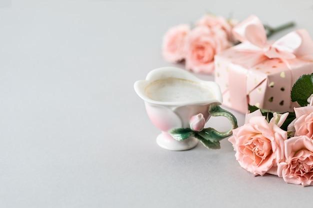 Filiżanka kawy, różowe róże, pudełko z prezentem i różowe róże na szarej powierzchni