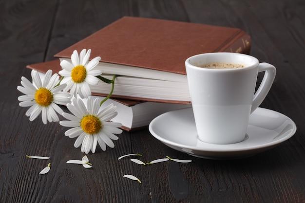 Filiżanka kawy, rumianek i książka na drewnianym stole
