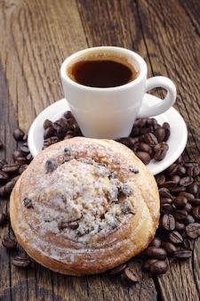 Filiżanka kawy, słodka bułka i ziarna kawy na drewnianym stole