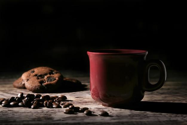 Filiżanka kawy, smaczne czekoladowe ciastko i ziarna kawy