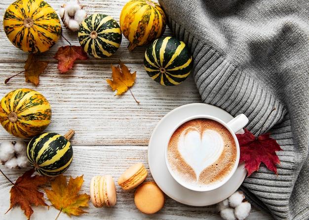 Filiżanka kawy, suche liście i szalik na stole. leżał płasko, widok z góry, miejsce na kopię