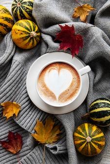 Filiżanka kawy, suche liście i szalik na stole. widok płaski, widok z góry