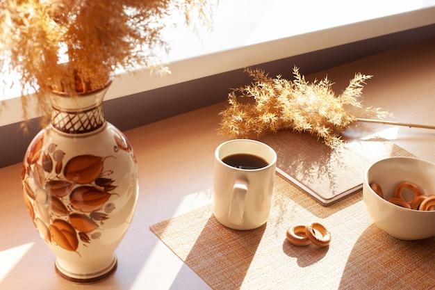 Filiżanka kawy, suszone kwiaty, baranki, notes na drewnianym stole. brązowe i białe.