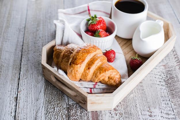 Filiżanka kawy, świeżo upieczone rogaliki i świeże truskawki na drewnianej tacy.