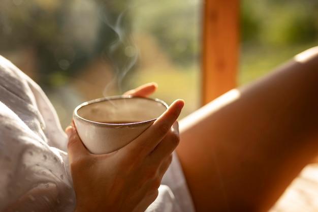Filiżanka kawy trzymając się za ręce z bliska