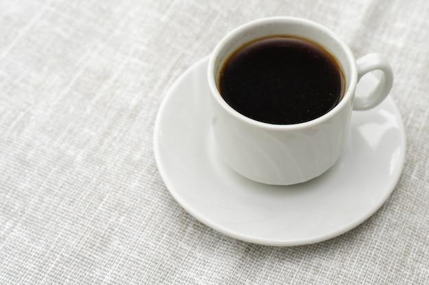 Filiżanka kawy w białej filiżance na jasnej powierzchni