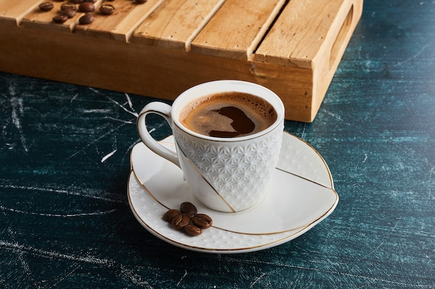 Filiżanka kawy w białym spodku.