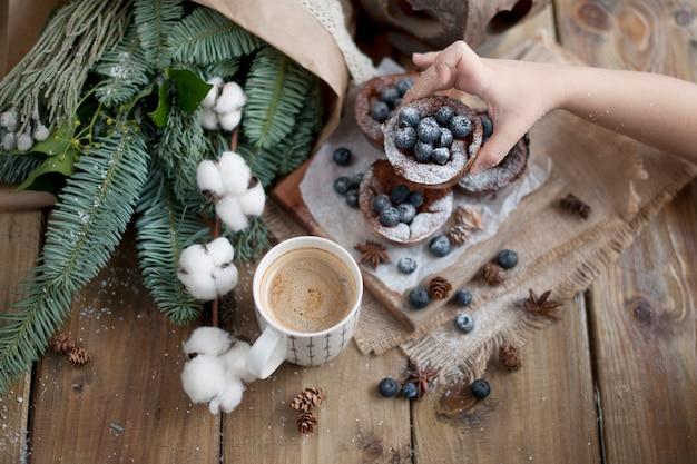 Filiżanka kawy w dłoni dziecka, drewniana i babeczki z jagodami