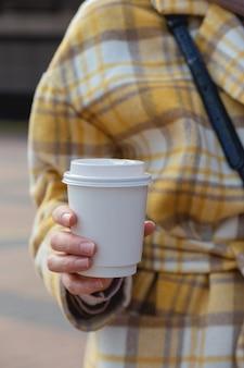 Filiżanka kawy w jednorazowej filiżance w rękach stylowej kobiety w makiecie projektu filiżanki miasta