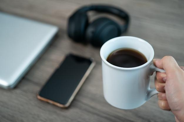 Filiżanka kawy w miejscu pracy biurko z inteligentny telefon, laptop na drewnianym stole.