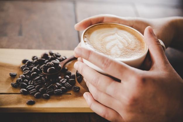 Filiżanka kawy w ręce kobiet na tekstury drewna.