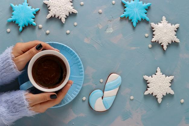 Filiżanka kawy w rękach kobiet i pierniki w kształcie płatków śniegu na jasnoniebieskim tle