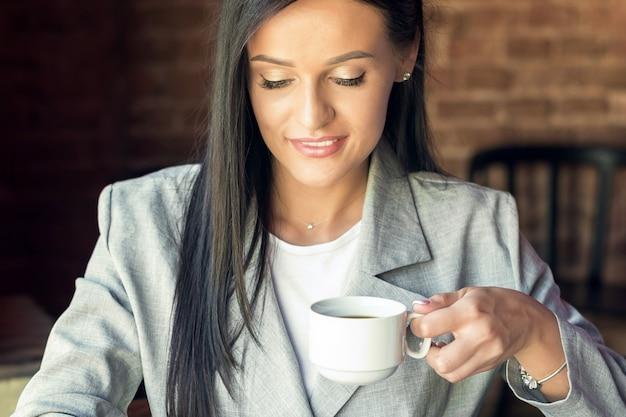 Filiżanka kawy w rękach kobiety.