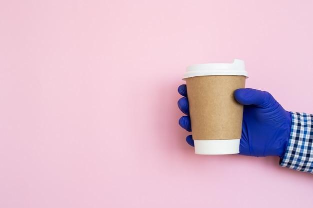 Filiżanka kawy w ręku na białym tle na różowym tle. ręka z kubek papierowy.
