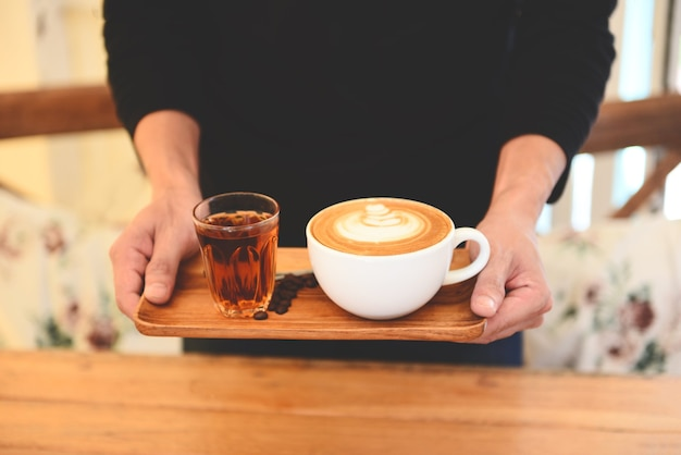 Filiżanka kawy w ręku na drewnianym stole w kawiarni z tłem ziaren kawy, serwowana kawa.