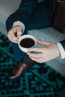 Filiżanka kawy w samiec wręcza zbliżenie