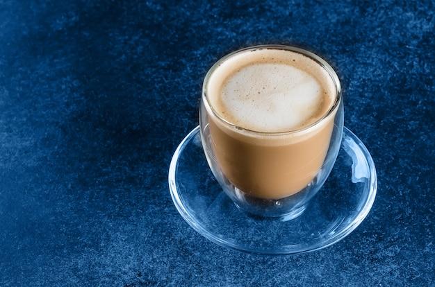 Filiżanka kawy w szklanej filiżance na błękitnym ciemnym tło stole. skopiuj miejsce poranny napój cappuccino