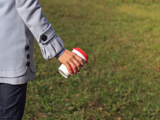 Filiżanka kawy wielokrotnego użytku w rękach na zielonym trawniku.