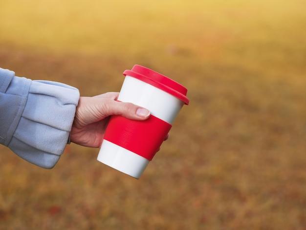 Filiżanka kawy wielokrotnego użytku w rękach