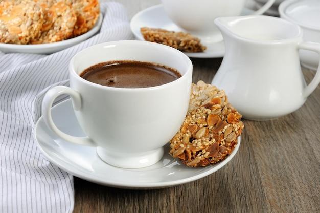 Filiżanka kawy z bezglutenowymi ciasteczkami zbożowymi na stoliku kawowym. czas coś przegryźć