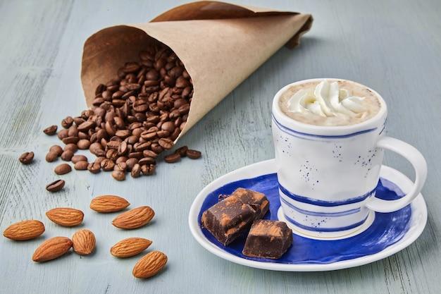 Filiżanka kawy z bitą śmietaną i ziarnami kawy