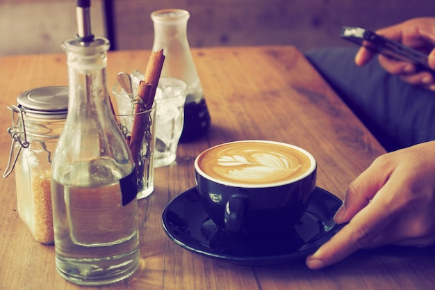 Filiżanka kawy z butelką wody i szkła z laski cynamonu na drewnianym stole