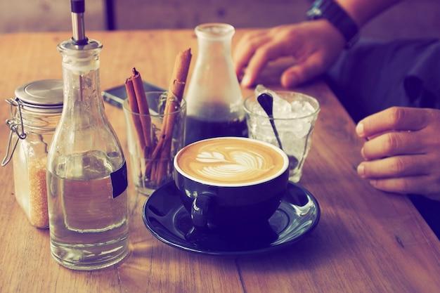 Filiżanka kawy z butelką wody i szkła z laski cynamonu